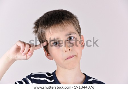 Young boy with the index finger on his head showing you that you are crazy and out of your mind