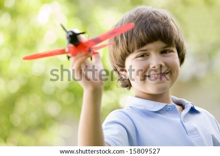 Young boy with toy airplane outdoors smiling