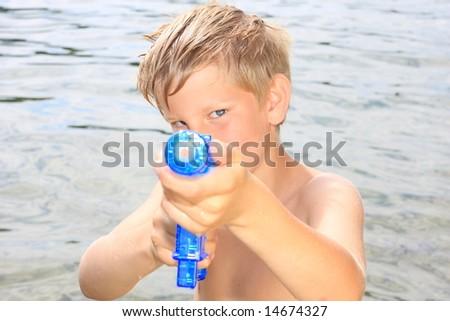 Young boy with water gun having fun