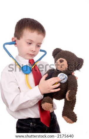 young boy with white shirt, stethescope and red tie giving a teddy bear a checkup