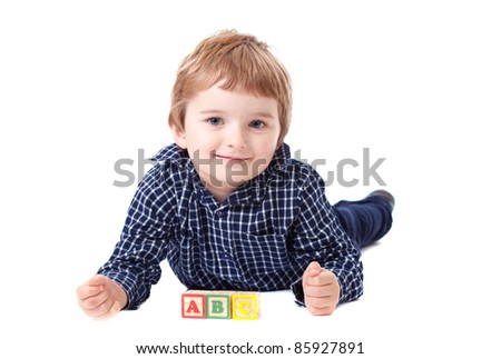 Young boy with wooden ABC blocks in front of him, isolated on white