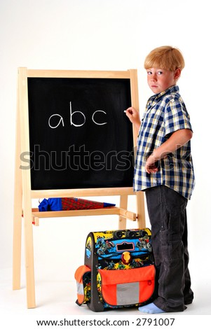 Young boy writing ABC in chalk on a blackboard on a white background