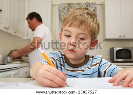Young boy writing while his father works in the kitchen