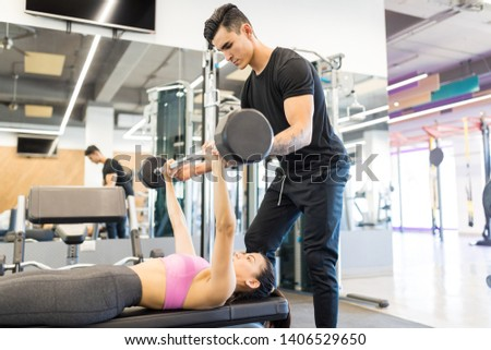 Young boyfriend supporting dedicated woman working out with barbell in health club