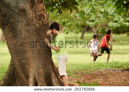 young boys and girls playing hide and seek in park, with kid counting leaning on tree