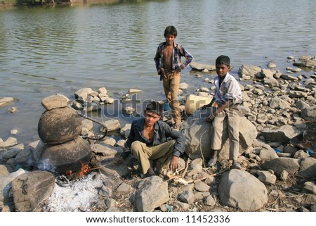 Young boys from the Kanjar tribal community in Chambal valley of Rajasthan State of India brewing illicit liquor on the riverbank