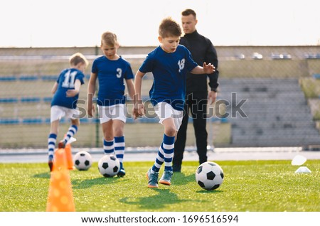 Young Boys in Sports Soccer Club on Training Unit. Kids Improve Soccer Skills on Natural Turf Grass Pitch. Football Practice Session for Children Youth Team. Junior Level Professional Soccer School