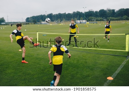 Young boys in youth soccer club playing football tennis training game. Teenage soccer players playing football tennis on training session. Teenagers practicing soccer on grass pitch.