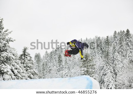 young boys jumping in air ind showing trick with snowboard at winter season #46855276