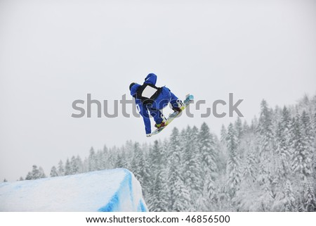 young boys jumping in air ind showing trick with snowboard at winter season #46856500