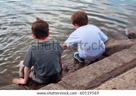 Young boys play beside lake