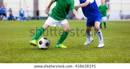 Young boys playing football soccer game on sports field. Running soccer players in sport shirts. Kids running and kicking soccer ball. #458638195