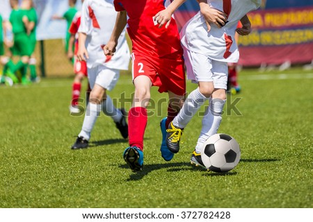 Young boys playing football soccer game. Running players in red and white uniforms