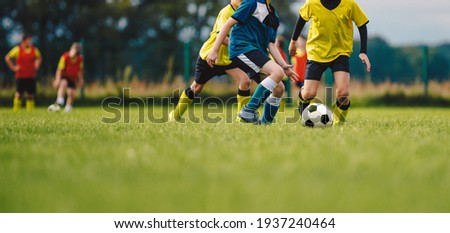 Young boys playing soccer game. Kids having fun in sport. Happy kids compete in football game. Running soccer players. Competition between players running and kicking football ball. Football school Foto d'archivio ©