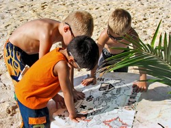 Young boys reading a pirate treasure map on the beach in Mexico