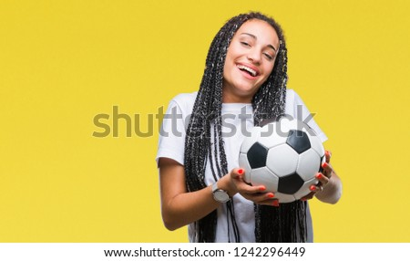 Young braided hair african american girl holding soccer ball over isolated background with a happy face standing and smiling with a confident smile showing teeth