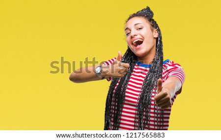 Young braided hair african american girl over isolated background approving doing positive gesture with hand, thumbs up smiling and happy for success. Looking at the camera, winner gesture. #1217565883