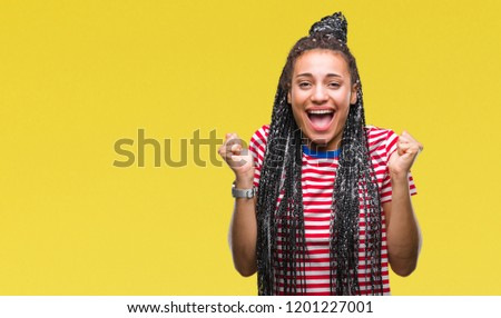 Young braided hair african american girl over isolated background celebrating surprised and amazed for success with arms raised and open eyes. Winner concept. #1201227001