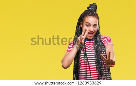 Young braided hair african american girl over isolated background smiling looking to the camera showing fingers doing victory sign. Number two. #1260953629