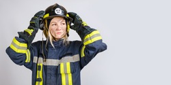 young brave woman in uniform of firefighter puts hardhat on her head and looking away on gray background, copy space for text