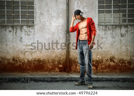 Young brawny man listening to music
