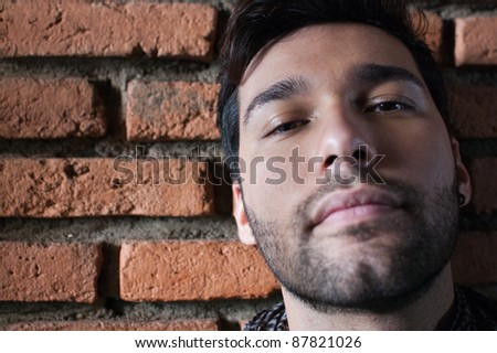 Young brazilian man against brick wall