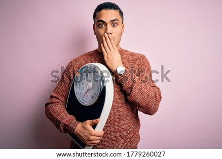 Young brazilian man doing diet to lose weigth holding scale over isolated pink background cover mouth with hand shocked with shame for mistake, expression of fear, scared in silence, secret concept Stock photo ©