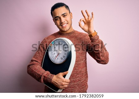 Young brazilian man doing diet to lose weigth holding scale over isolated pink background doing ok sign with fingers, excellent symbol Stock photo ©