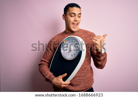 Young brazilian man doing diet to lose weigth holding scale over isolated pink background pointing and showing with thumb up to the side with happy face smiling Stock photo ©