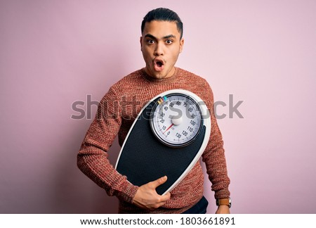 Young brazilian man doing diet to lose weigth holding scale over isolated pink background scared in shock with a surprise face, afraid and excited with fear expression Stock photo ©