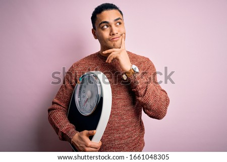 Young brazilian man doing diet to lose weigth holding scale over isolated pink background serious face thinking about question, very confused idea Stock photo ©