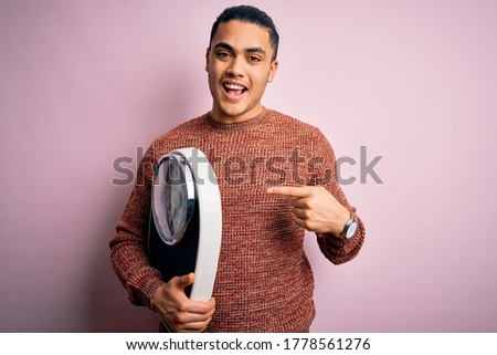Young brazilian man doing diet to lose weigth holding scale over isolated pink background very happy pointing with hand and finger Stock photo ©
