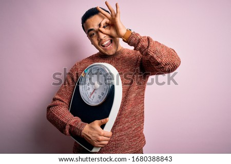 Young brazilian man doing diet to lose weigth holding scale over isolated pink background with happy face smiling doing ok sign with hand on eye looking through fingers Stock photo ©