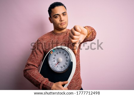 Young brazilian man doing diet to lose weigth holding scale over isolated pink background with angry face, negative sign showing dislike with thumbs down, rejection concept Stock photo ©
