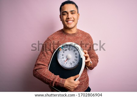 Young brazilian man doing diet to lose weigth holding scale over isolated pink background with a happy face standing and smiling with a confident smile showing teeth Stock photo ©