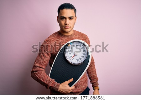 Young brazilian man doing diet to lose weigth holding scale over isolated pink background with a confident expression on smart face thinking serious Stock photo ©