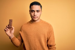 Young brazilian man eating healthy energy bar with protein over isolated yellow background with a confident expression on smart face thinking serious