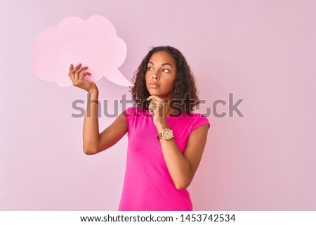 Young brazilian woman holding cloud speech bubble standing over isolated pink background serious face thinking about question, very confused idea