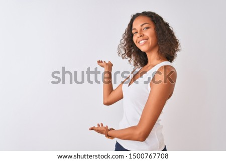 Young brazilian woman wearing casual t-shirt standing over isolated white background Inviting to enter smiling natural with open hand