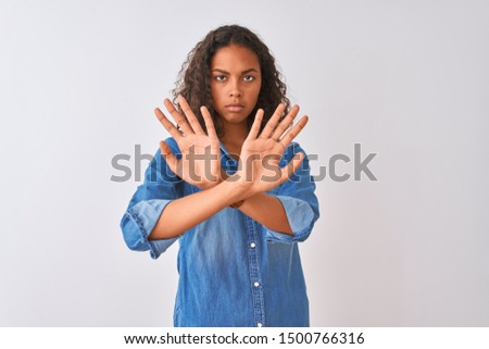 Young brazilian woman wearing denim shirt standing over isolated white background Rejection expression crossing arms and palms doing negative sign, angry face
