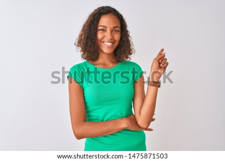 Young brazilian woman wearing green t-shirt standing over isolated white background with a big smile on face, pointing with hand and finger to the side looking at the camera.