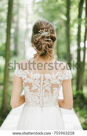 Young bride and details of her gown: elegant back of wedding dress and hair accessories