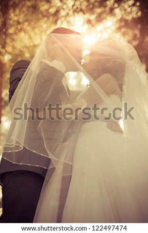 young bride and groom in the park, a wedding bouquet, wedding dresses