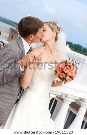 young bride and groom kissing outdoor