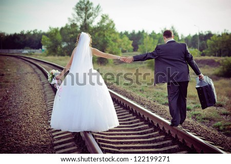 young bride and groom on a railway track