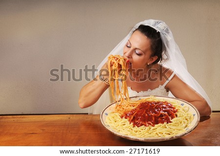 young bride eats spaghetti with tomato in rustic setting