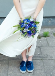 Young bride holding a bouquet of cornflowers. Blue sneakers. Very shallow depth of field, tilt-shift effect.