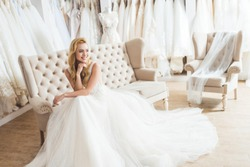 Young bride in tulle dress sitting on sofa in wedding salon