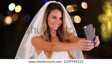 Young bride in wedding dress and veil taking a selfie with cell phone outside