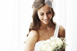Young bride in wedding dress holding bouquet, studio shot